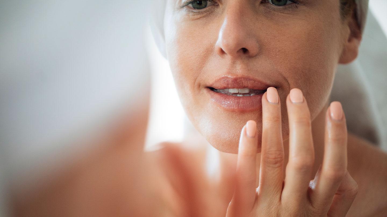 Trockene Lippen: Frau mittleren Alters berührt mit den Fingern ihre Lippen und betrachtet sich im Spiegel.
